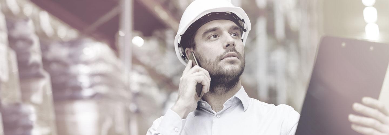 Man wearing hard hat holding a clipboard